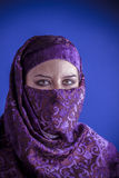 Beautiful arabic woman with traditional veil on her face, intens. E look,purple Royalty Free Stock Image
