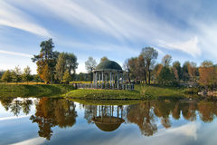 Beautiful arbor in the park. Idyllic autumn landscape. Lake with island and arbor with colorful trees and sky reflection Royalty Free Stock Photography