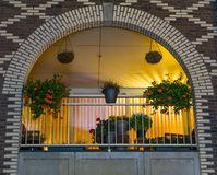 Beautiful arched dutch balcony decorated with flowers at night, modern city buildings and architecture stock image