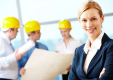 Beautiful architect. Portrait of beautiful architect folding arms on the background of workers Stock Photo