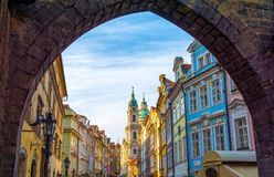 Beautiful architecture in old part of Prague - Mala Strana, Czech republic. View on baroque church and buildings on Mala Strana in Prague under arch Royalty Free Stock Image