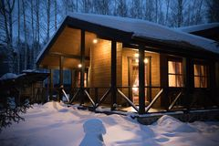 A beautiful architectured modern house in winter forest. Evening time