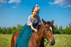Beautiful aristocrat in a dress on a horse.  royalty free stock image