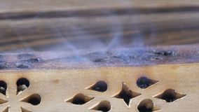 Beautiful aroma smoke near the figurine. uddha Figure On Wooden Tea Board Chaban With An Aroma Smoke. Macro Close Up Of. Burning Incense Sticks With Smoke Over Royalty Free Stock Images