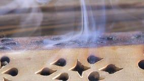 Beautiful aroma smoke near the figurine. uddha Figure On Wooden Tea Board Chaban With An Aroma Smoke. Macro Close Up Of royalty free stock photos