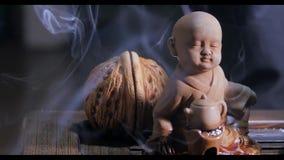 Beautiful aroma smoke near the figurine. uddha Figure On Wooden Tea Board Chaban With An Aroma Smoke. Macro Close Up Of stock video footage