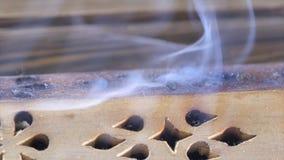 Beautiful aroma smoke near the figurine. uddha Figure On Wooden Tea Board Chaban With An Aroma Smoke. Macro Close Up Of. Burning Incense Sticks With Smoke Over Royalty Free Stock Photos