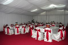 Wedding arrangement with white and red chairs awaiting guests royalty free stock photography