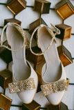 Beautiful art deco inspired evening leather shoes in beige color with golden sparkling bows and straps royalty free stock images