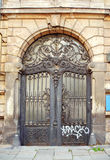 Beautiful art nouveau door gate with ugly graffiti. Beautiful art nouveau door gate with iron flower motives and ugly graffiti Royalty Free Stock Photos