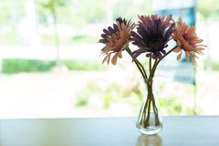 Beautiful artificial flower in small glass vase Stock Images
