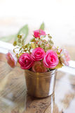 Beautiful artificial pink flowers. Artificial roses in aluminium pot on  table Royalty Free Stock Photography