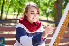 Beautiful artist draws a picture in a good mood outdoors. Royalty Free Stock Photos