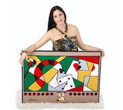Beautiful artist holding with two hands her painting Obsession. Beautiful woman artist kneeling on a white rug and holds with two hands her painting Obsession on royalty free stock image