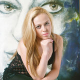 Beautiful artist in the studio. In front of her picture Stock Photography