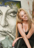 Beautiful artist in the studio. In front of her picture Royalty Free Stock Photos