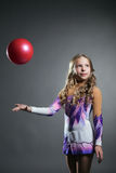 Beautiful artistic gymnast throws ball in studio Royalty Free Stock Photography