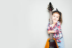 Beautiful artistic little girl playing guitar on grey background. Place for your text stock images