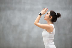Beautiful Ashtanga Vinyasa Yoga. Side view portrait of beautiful young woman wearing sport watch for heart rate and calorie burn control working out against grey Stock Images