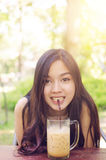 Beautiful asia woman smile and drink coffee. Warm light flare effect on top from the sun Stock Photo