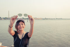 Beautiful Asia woman traveler,holds in hand sunglasses ,holidays Stock Image