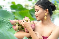 Beautiful asia women wearing traditional Thai dress and sitting on wooden boat in flower lotus lake. Her hands are holding a pink. Beautiful asia woman wearing stock photos