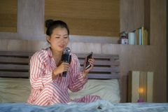 Beautiful Asian American teenager girl singing karaoke song excited at home bedroom holding mobile phone playing on bed excited stock photography