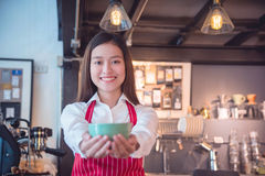 Barista holding coffee cup and smiles Royalty Free Stock Photography