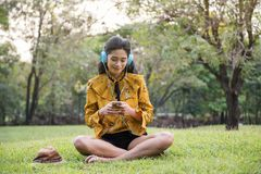 Boho female hispter relax in park. Beautiful Asian Bohemian girl with boho style dress relax in park, play social media, listen music by smartphone. Attractive Stock Images