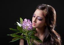 Beautiful asian bride. Holding purple flowers, isolated on black Stock Image