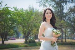 Beautiful asian bride in park Stock Images