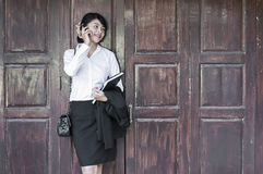 Beautiful Asian business woman calling mobile phone. Beautiful Asian business woman calling mobile phone in front of old wooden door Royalty Free Stock Photo