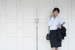 Beautiful Asian business woman calling mobile phone. Beautiful Asian business woman calling mobile phone in front of white wooden door Stock Photo