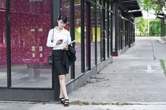 Beautiful Asian business woman calling mobile phone. Beautiful Asian business woman calling mobile phone in shopping mall Royalty Free Stock Images