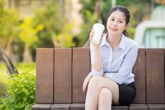 Beautiful asian business woman drinking coffee on park bench Royalty Free Stock Photos