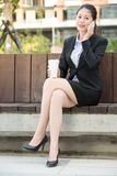 Beautiful asian business woman drinking coffee use smart phone Royalty Free Stock Images
