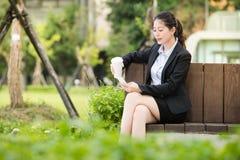 Beautiful asian business woman drinking coffee use smart phone Stock Photo