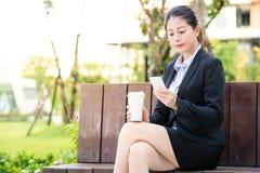 Beautiful asian business woman drinking coffee use smart phone Stock Photos