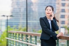 Beautiful asian business woman drinking coffee use smart phone Royalty Free Stock Photos