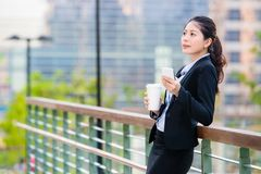 Beautiful asian business woman drinking coffee use smart phone Royalty Free Stock Photography