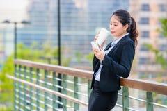 Beautiful asian business woman drinking coffee use smart phone Stock Image