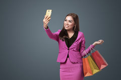 Beautiful asian business woman with her smartphone holding shopp Royalty Free Stock Images