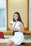 Beautiful Asian business woman holding coffee cup at her desk Stock Photo