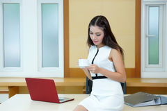Beautiful Asian business woman holding coffee cup at her desk Royalty Free Stock Image