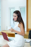 Beautiful Asian business woman holding coffee cup at her desk. In office Royalty Free Stock Image