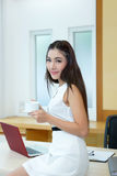Beautiful Asian business woman holding coffee cup at her desk. In office Stock Photos