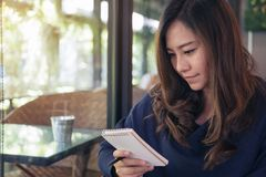 A beautiful Asian business woman holding and looking at notebook. In cafe Royalty Free Stock Photography