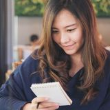 A beautiful Asian business woman holding and looking at notebook. In cafe Royalty Free Stock Photo