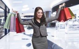 Beautiful asian business woman holding many shopping bag Stock Photos