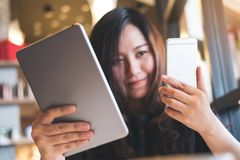 A beautiful Asian business woman holding tablet pc and smart phone while working Stock Photos